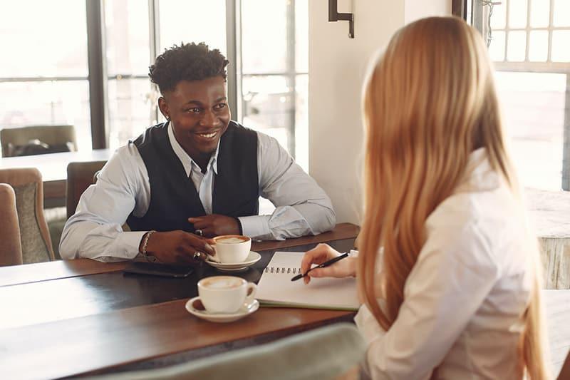 Ein Paar trinkt einen Kaffee, während es über seine Arbeit spricht