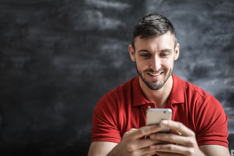 ein positiver Mann in einem roten Poloshirt mit einem Smartphone