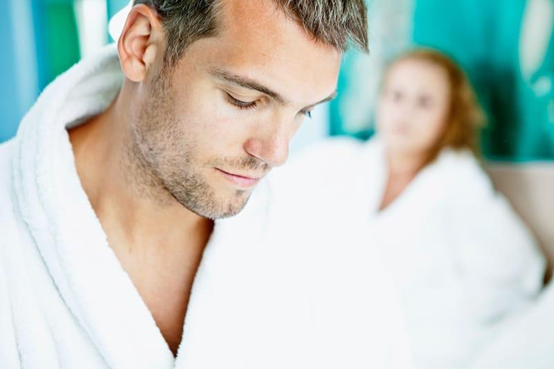 Ein trauriger Mann im Bademantel schaut nach unten, während er neben einer Frau auf dem Bett sitzt