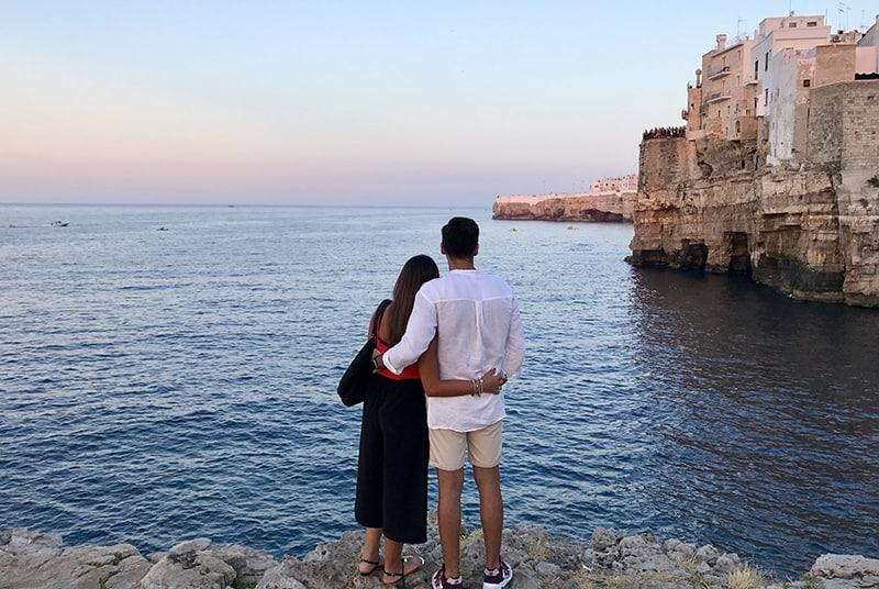 ein umarmendes Paar, das auf der Klippe in der Nähe des Meeres steht