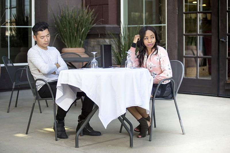 ein unglückliches Paar, das ohne Unterhaltung im Restaurant sitzt