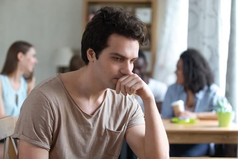ein verärgerter nachdenklicher Mann, der allein getrennt von Freunden hinter ihm sitzt