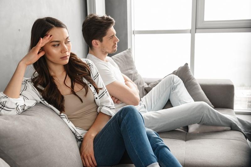 ein verärgertes Paar, das ohne Unterhaltung zusammen auf der Couch sitzt