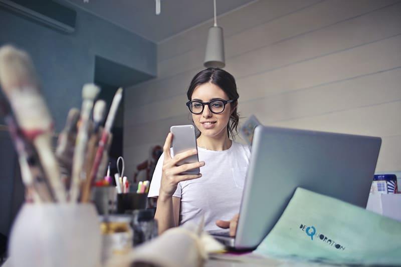 eine überraschte Frau, die auf das Smartphone schaut, während sie am Schreibtisch sitzt