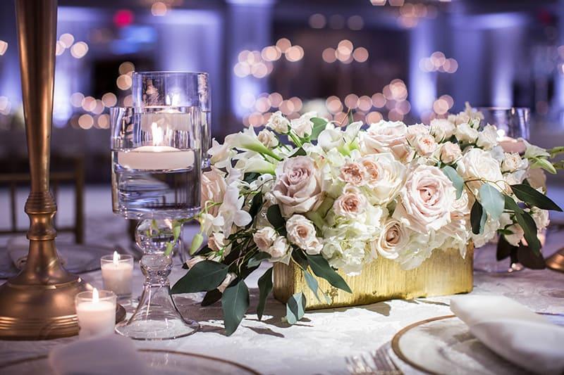 eine Dekoration mit rosa Rosen in der Box auf dem Tisch