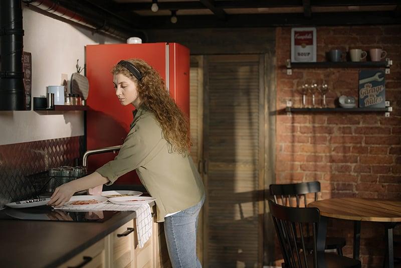 eine Frau, die am Waschbecken steht und Teller wäscht