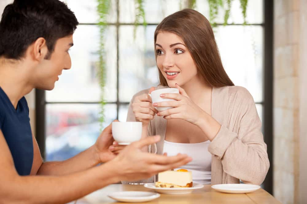 eine Frau, die überrascht aussah und einen Mann ansah, während sie eine Tasse Kaffee hielt