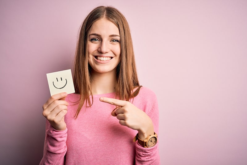 eine Frau, die Erinnerungspapier mit Lächeln-Emoji-Nachricht hält und mit dem Finger auf das Papier zeigt