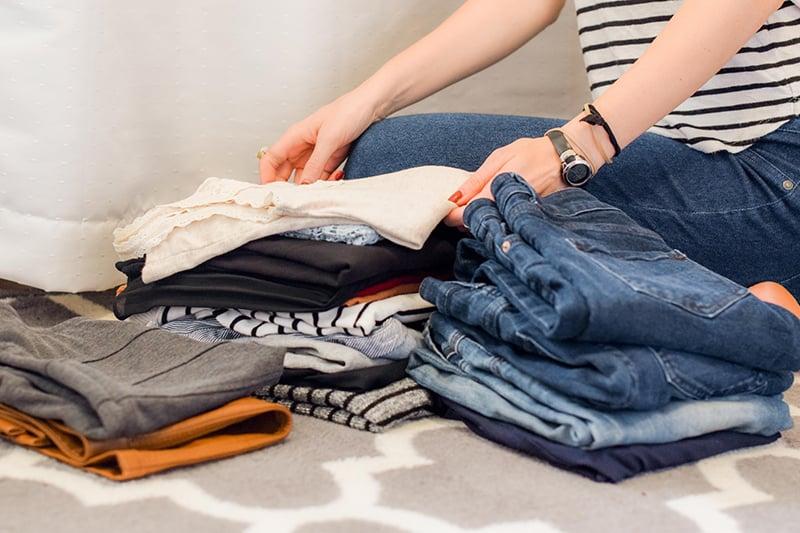 eine Frau, die Kleidung organisiert, während sie auf dem Bett sitzt