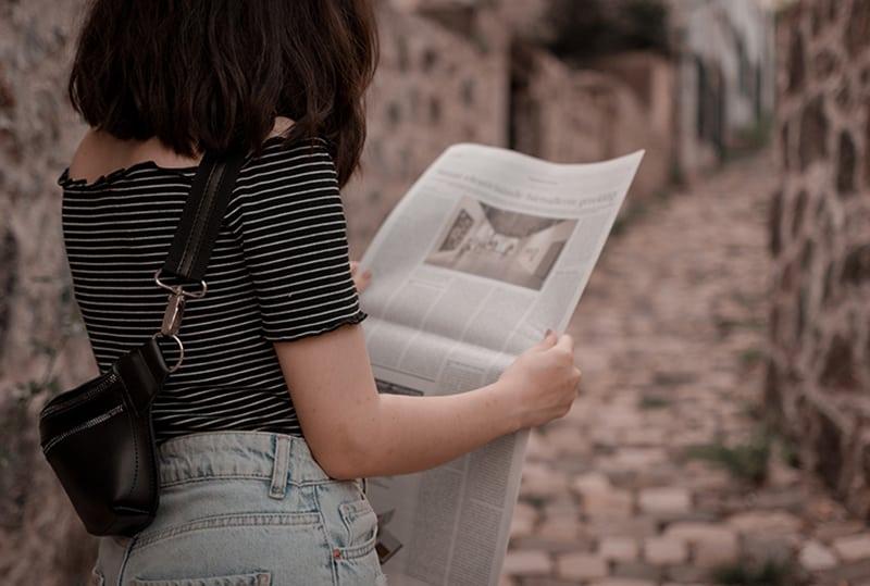 eine Frau, die Zeitung liest, während sie auf der Straße steht