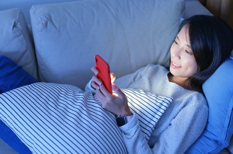 eine Frau, die abends auf der Couch liegt und ein Smartphone benutzt
