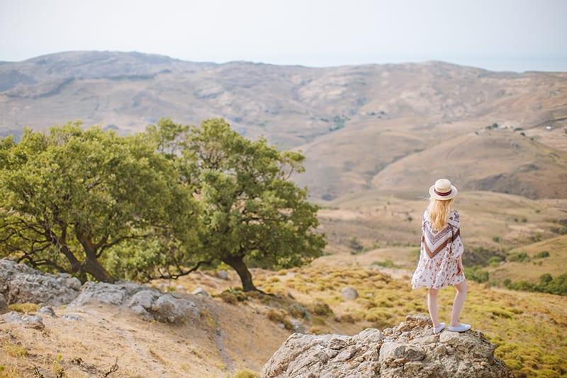 eine Frau, die auf dem Felsen im Tal steht