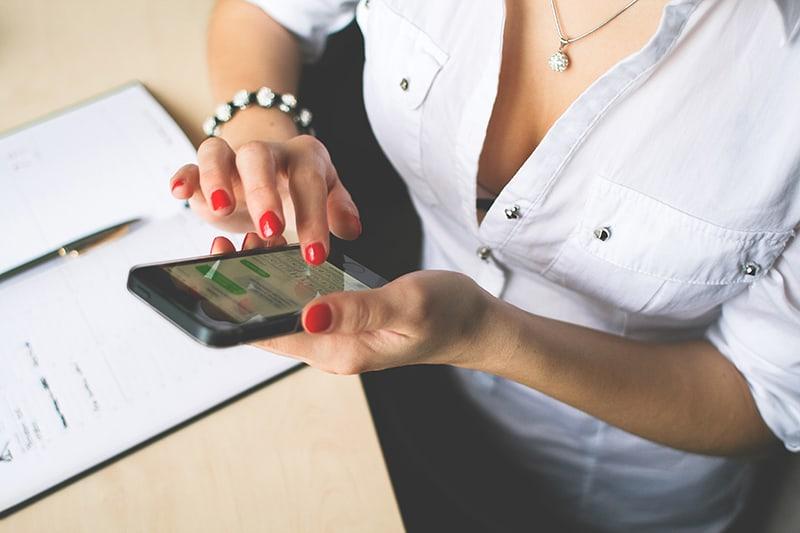 eine Frau, die auf dem Smartphone tippt, während sie am Schreibtisch sitzt