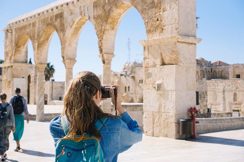 eine Frau, die auf ihrer Reise ein Foto von den Ruinen macht