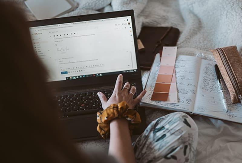 eine Frau, die eine E-Mail auf dem Laptop liest, während sie auf dem Bett sitzt