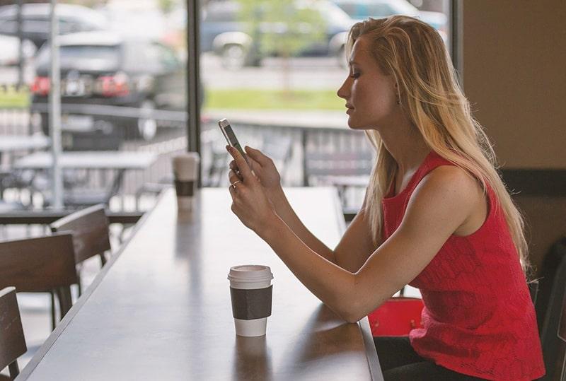 eine Frau, die eine Nachricht auf ihrem Smartphone liest, während sie in einem Café sitzt