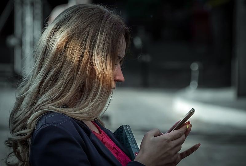 eine Frau, die eine Nachricht auf ihrem Smartphone tippt, während sie draußen steht