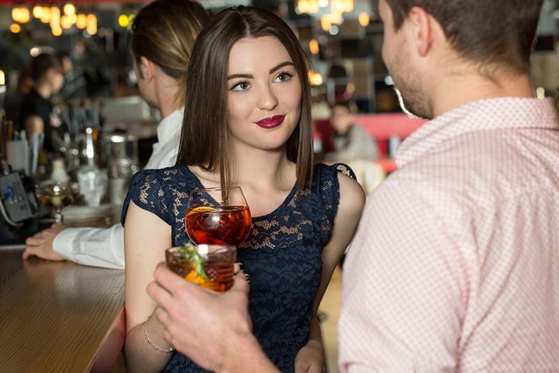 eine Frau, die einem Mann direkt in die Augen schaut während beide mit einem Glas Getränk rösten
