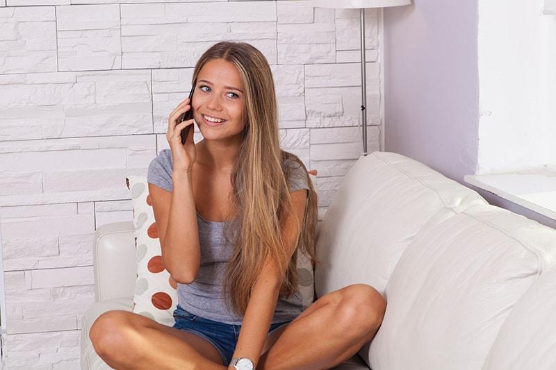 eine Frau, die einen Anruf hat, der auf der Couch sitzt