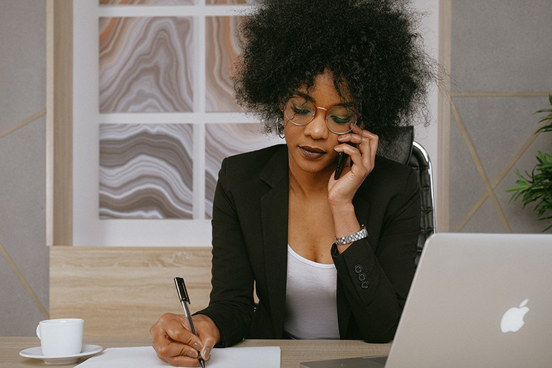 eine Frau, die einen Anruf hat, während sie in einem Büro bei der Arbeit sitzt