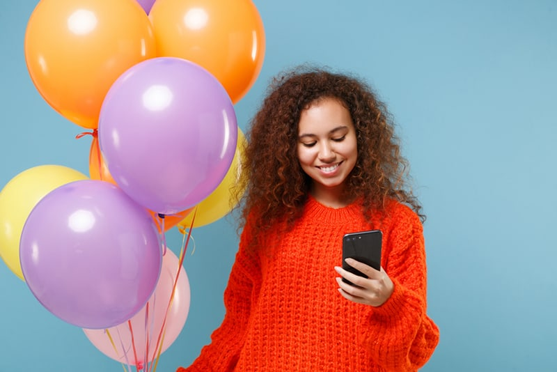 a woman celebrating a birthday holding a smartphone and standing near the balloons