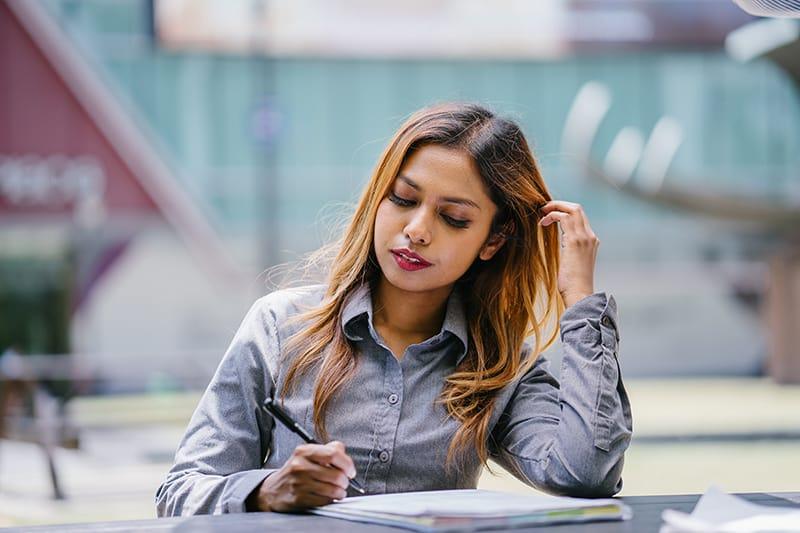 eine Frau, die einen Stift hält und ihre Haare berührt, während sie am Tisch sitzt