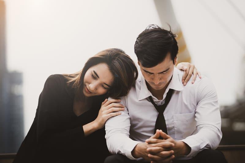 eine Frau, die einen verärgerten Mann ermutigt und ihn umarmen