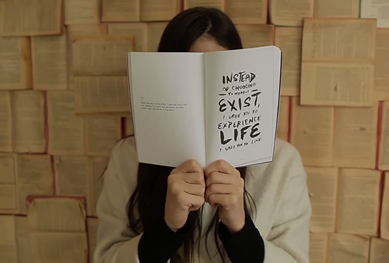 eine Frau, die ihr Gesicht mit einem weit geöffneten Buch bedeckt