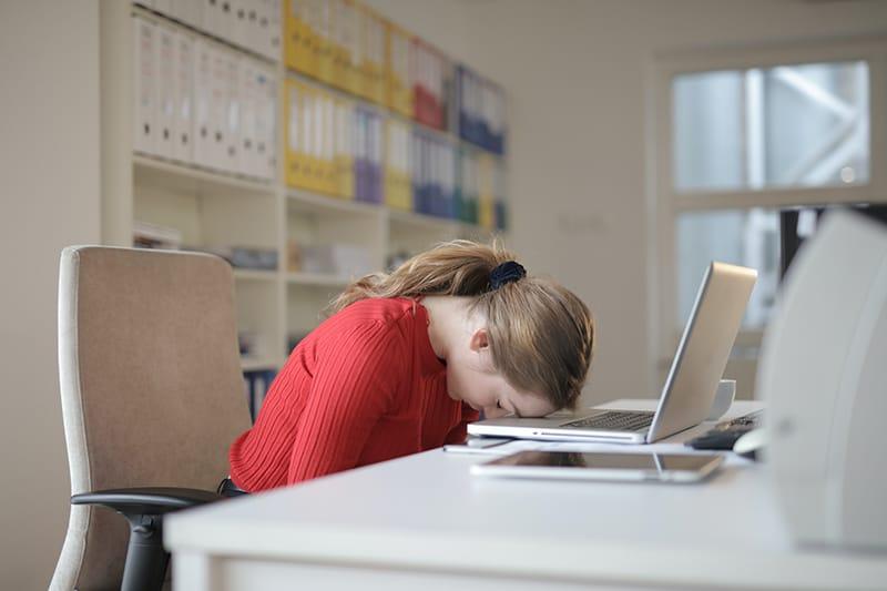 Eine Frau lehnte ihren Kopf an einen Laptop, während sie am Schreibtisch saß