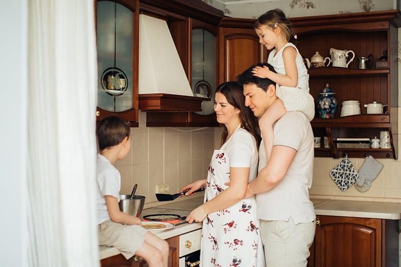 eine Frau, die mit ihrem Mann und ihren Kindern in der Küche kocht