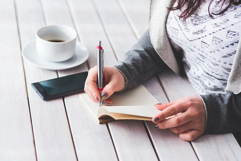 eine Frau, die in ein Notizbuch schreibt, während sie am Tisch sitzt