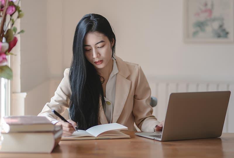 eine Frau, die in ein Notizbuch schreibt, während sie im Büro arbeitet