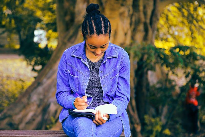 eine Frau, die in ein Notizbuch schreibt, während sie auf der Bank sitzt