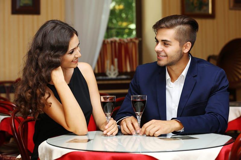 eine Frau, die mit einem Mann bei einem Date in einem Restaurant flirtet