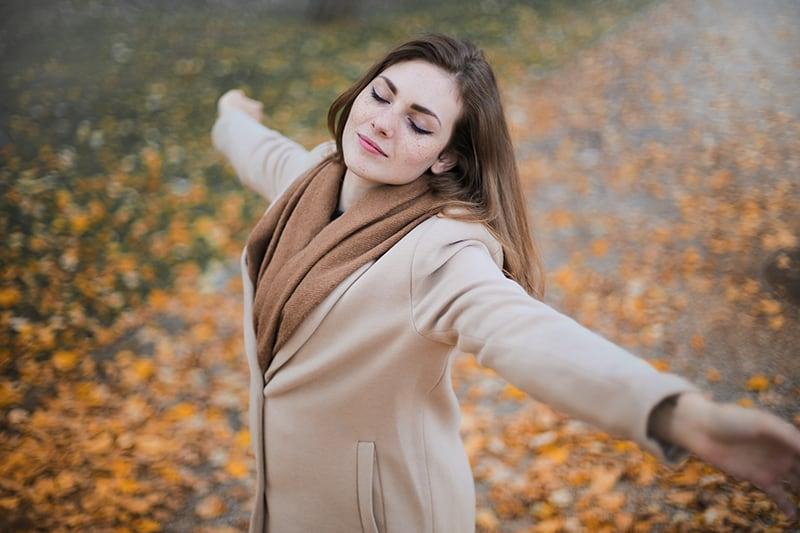 Eine Frau fühlte sich erleichtert, als sie im Park ihre Arme ausbreitete