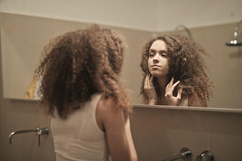 eine Frau, die sich im Badezimmer im Spiegel betrachtet