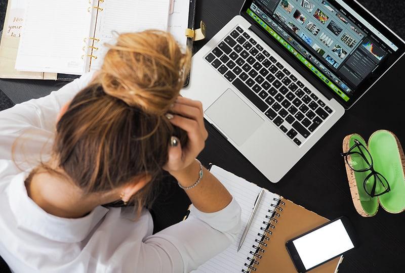 Eine Frau, die sich stressig fühlt, sitzt am Schreibtisch im Büro