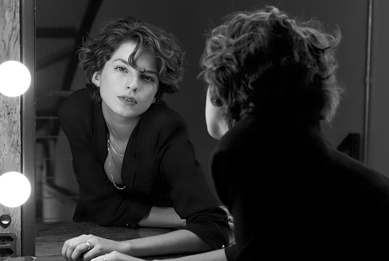 eine Frau, die sich vor den Spiegel lehnt und nachdenklich aussieht