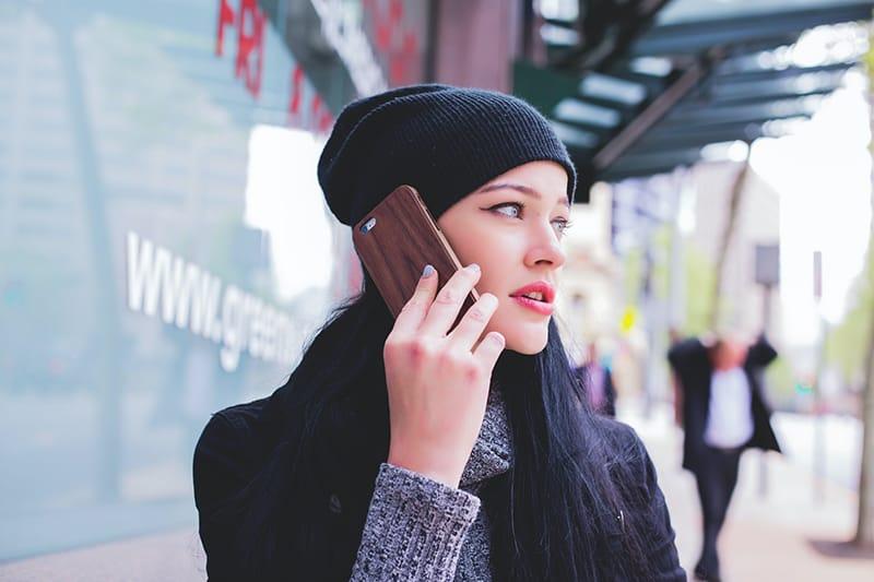 eine Frau, die einen Anruf tätigt, während sie auf dem Bürgersteig steht
