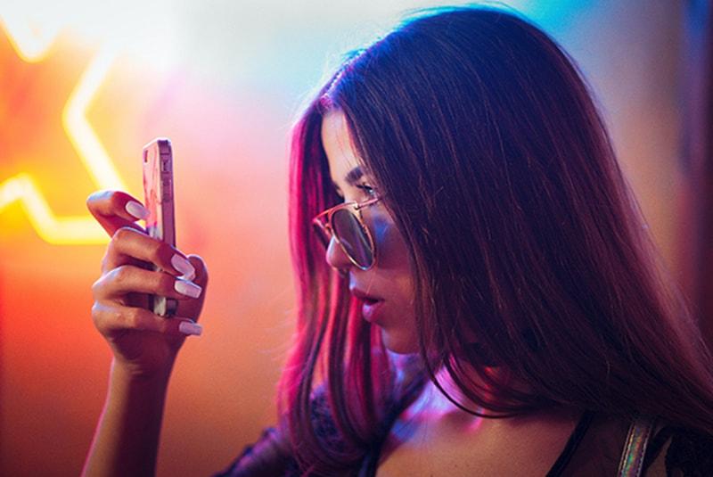 eine Frau, die Smartphone mit Unglauben betrachtet, während sie in der Nähe von Neonlichtern steht