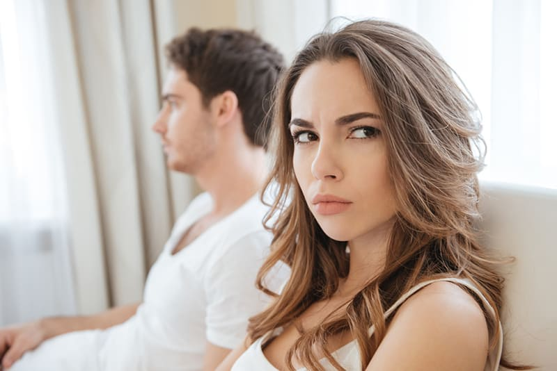 eine Frau, die verärgert aussieht, während sie neben einem Mann sitzt