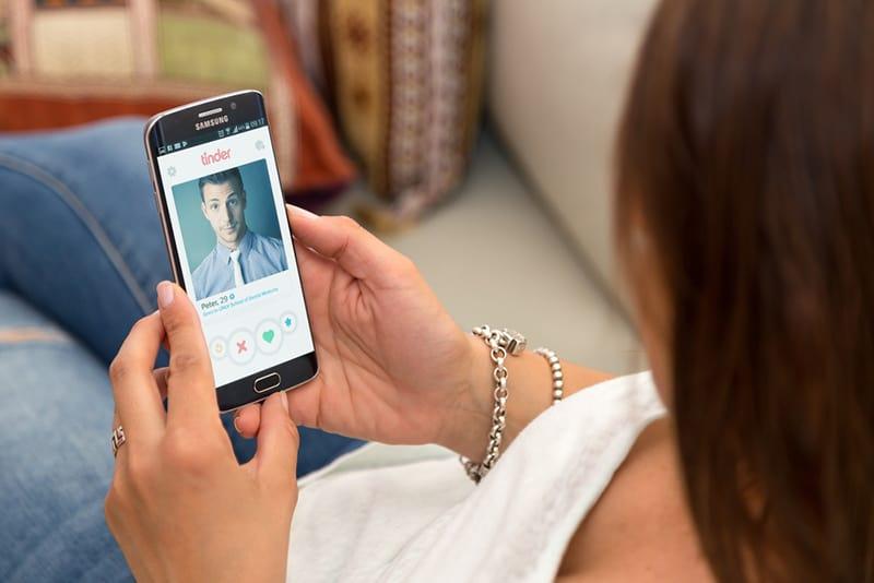 eine Frau, die zu Hause in einem Sessel ruht und ein Smartphone mit Tinder auf dem Bildschirm hält