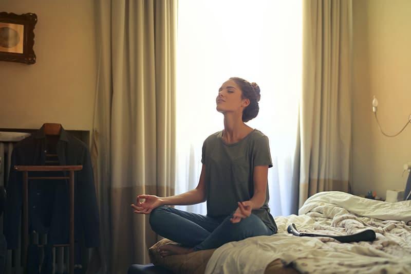 eine Frau, die in einem Haus meditiert, während sie im Schlafzimmer sitzt