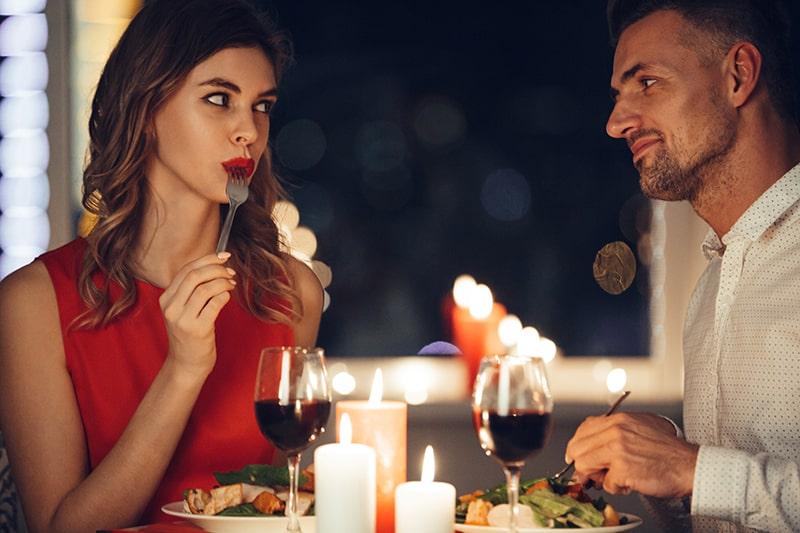 Eine Frau im roten Kleid isst und flirtet mit ihrem Mann beim romantischen Abendessen