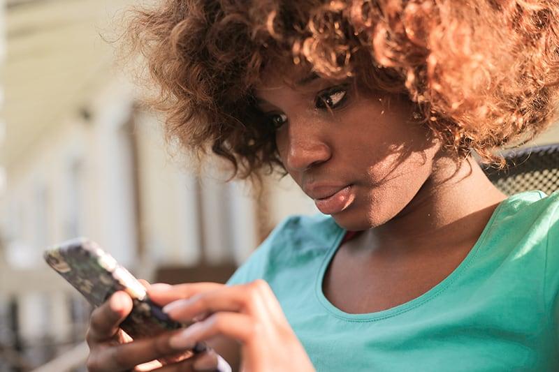 eine Frau in einem blauen Hemd, die ein Smartphone benutzt, während sie draußen steht