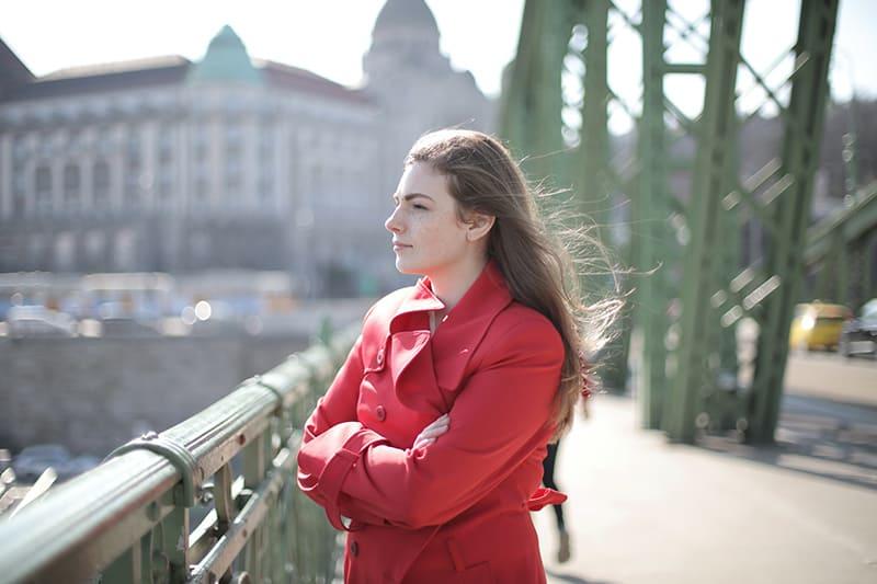 eine Frau in einem roten Mantel, die nahe Metallgeländern auf der Brücke steht und den Fluss betrachtet