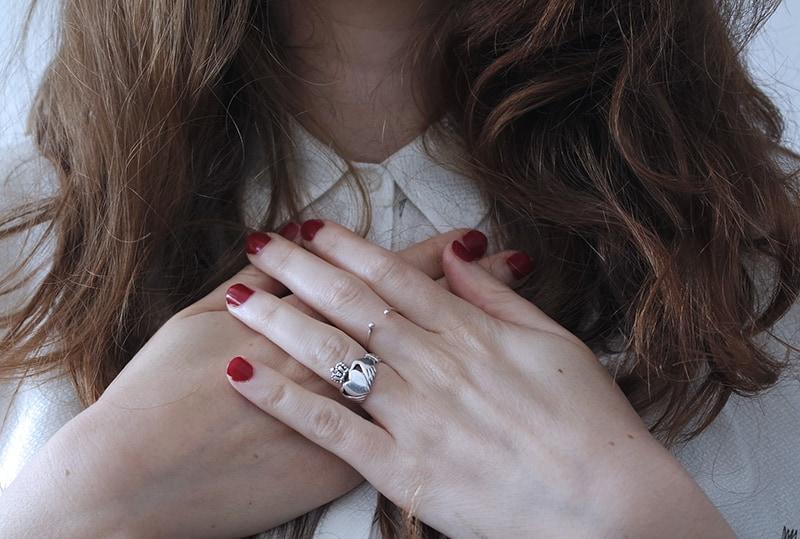 eine Frau, die ein weißes Hemd trägt, während sie ihre Brust mit Handflächen berührt