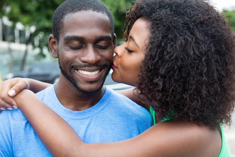 eine Frau küsste einen lächelnden Mann auf die Wange und umarmte ihn