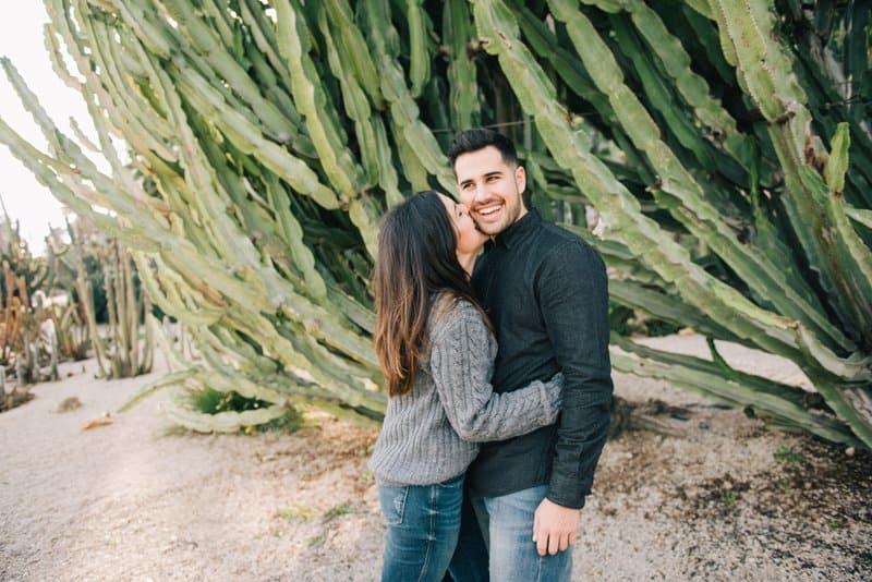 eine Frau küsst ihren lächelnden Mann