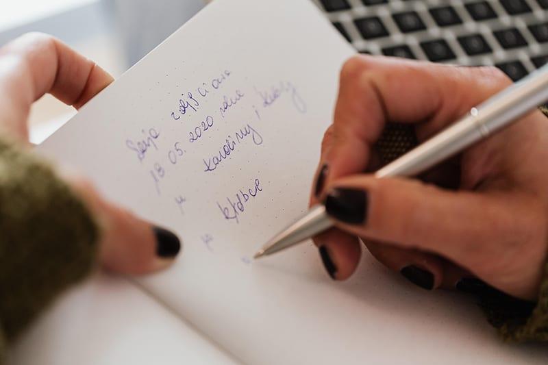 eine Frau, die einen Stift hält, während sie in das Notizbuch schreibt